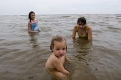 One-year-old Rebecca Nata, foreground, joins Maggie Duplantier, 11, and Veronica Nata, 12, in the Gulf waters off Waveland Beach, Miss., a day after crews removed tar balls that had washed ashore.