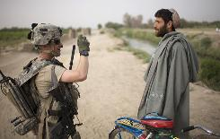 U.S. Army 1st Lt. Christopher Babcock from New Orleans photographs an Afghan villager who was stopped  cycling in the Arghandab Valley of Afghanistan on Thursday.