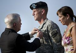 Annie McChrystal stands with her husband, Gen. Stanley McChrystal, as he is awarded the Department of Defense Distinguished Service Medal by Secretary of Defense Robert Gates during a retirement ceremony at Fort McNair on Friday.