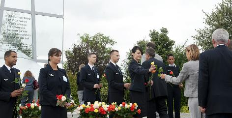 "Air France hostesses give flowers to relatives of victims and crew during a ceremony on Sunday in front of a memorial plaque that reads """"On July 25, 2000, the Concorde crashed in Gonesse, taking the life of 113 people aboard and on the ground."""