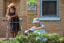 Volunteer Margaret Missiaen tends a garden in the yard of Maurine Phinisee, 90, left, who is back in her Washington, D.C., home with the help of Capitol Hill Village.