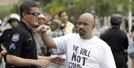 A Phoenix police officer prepares to arrest a demonstrator in front of the U.S. District Courthouse in Phoenix last week while the court considered a lawsuit against the anti-illegal-immigration statute.