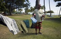With the beach behind him, Tony Williams hangs his laundry between two palm trees, July 12, in Honolulu. Homelessness increased 15 percent on Oahu since last year according to a recent report.