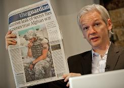 Julian Assange, Australian founder of whistleblowing website Wikileaks, holds up a copy of Monday's Guardian newspaper during a press conference in London.