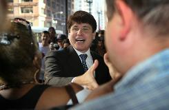 Former Illinois Gov. Rod Blagojevich greets supporters as he arrives for court Tuesday in Chicago.