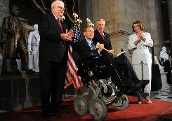 Rep. Jim Langevin, D-R.I., center, holds the Speaker's gavel with Rep. James Sensenbrenner, left, R-Wis., Rep. Steny Hoyer, D-Md., and Speaker of the House Nancy Pelosi, D-Calif., at a reception to mark the 20th anniversary of the Americans with Disabilities Act on July 26 in Statuary Hall on Capitol Hill in Washington, D.C. Rep. Langevin, the first quadriplegic to serve in Congress, presided over the House today, marking the first time a member in a wheelchair has ever done so.