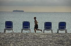 A man takes a morning jog along the beach in Miami. Running is better than cycling at boosting metabolism.