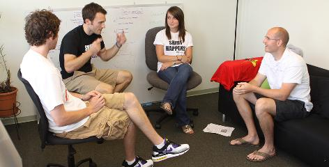 """Intern Stephanie Durphey, 21, wears one of her company's """"Shirt Happens"""" items during a meeting with CreateMyTee.com's president, Josh Fales, 27, right, vice president of marketing Chad Eckert, 25, left, and vice president of sales, Nick Shelton, 24, in Ann Arbor, Mich. Like many U.S. college students, Durphey is not paid for her work as an intern."""