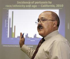 Dr. Juan Ruiz, of the California Department of Public Health, speaks at a CDC news conference earlier in July to publicize a recent, sharp increase in the number of pertussis, or whooping cough, cases.
