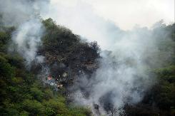 Fire and smoke rise from the wreckage of a passenger plane in the Margalla Hills on the outskirts of Islamabad on Wednesday.