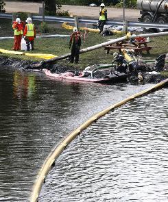 Crews work on a boom in the Kalamazoo River in Battle Creek, Mich., trying to capture oil from a ruptured pipeline, owned by Enbridge Inc., Thursday.