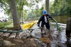 Raul Vervuzco of Eagle Services uses a suction hose to clean oil from atop the Kalamazoo River on Wednesday in a containment area in Augusta, Mich.