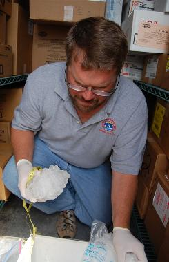 James Scarlett, meteorologist in charge at the National Weather Service in Aberdeen, S.D., holds a hailstone that may be among the world's largest in the walk-in freezer of the Coffee Cup Fuel Stop in Vivian, S.D.