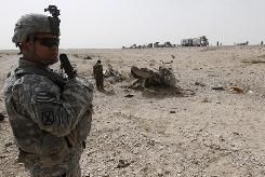 A U.S. soldier stands by the wreckage of a bus that was hit by a roadside bomb outside Kandahar, south of Kabul, on Sunday.