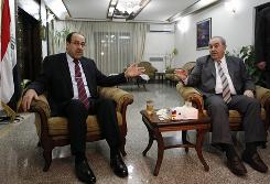 Iraqi Prime Minister Nouri al-Maliki, left, meets with Ayad Allawi, a former prime minister, on June 29 at Allawi's compound in Baghdad. Both men have claimed the right to form a new government following March parliamentary elections.