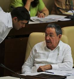Cuban President Raul Castro talks with his grandson and bodyguard Raul Dominguez Castro, during the 5th Legislature of the Cuban National Assembly at the Parliament in Havana on August 1.