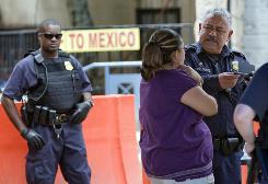 A Customs and Border Patrol officer stops a woman leaving Arizona for Mexico in Nogales, Ariz., on Monday. 