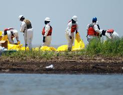 Workers clean tar balls form the Gulf oil spill off a beach in South Pass, La., on May 12.