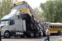 Rescue workers check the scene of an accident involving two school buses of band students and a tractor-trailer Thursday near Gray Summit, Mo.