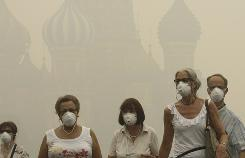 Tourists wear protective face masks as they walk along the Red square in thick smog, with Saint Basil's Cathedral partially visible in the back, in Moscow, Russia, Friday.