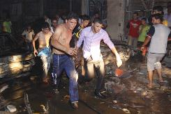 Iraqi men evacuate a victim from the scene of an explosion in Basra, Iraq's second-largest city, 340 miles southeast of Baghdad, Iraq, Saturday.