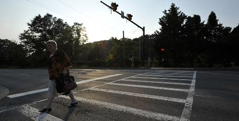 Deborah Williams crosses Van Dorn Street in Alexandria, Va., where there's a High-intensity Activated Cross Walk or HAWK.