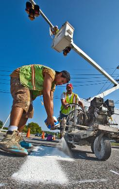 Charlie Clark, left, and Richard Adcox paint a crosswalk to accompany a new traffic signal on Route 72 in Newark, Del.