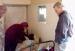 Tom Little, right, optometrist and team leader with the International Assistance Mission, watches as a doctor examines a patient in an Afghanistan clinic.