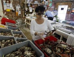 Connie Plessala organizes Louisiana blue crabs into bins at Big Fisherman Seafood in New Orleans.