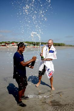 "Ed Stafford, of England, right, and Gadiel ""Cho"" Sanchez Rivera, of Peru, celebrate arriving to Crispim beach in Marapanim in Brazil's Para state, Monday."
