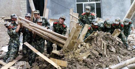 Workers leverage debris to search for people missing in landslides in Zhouqu County, an ethnically Tibetan area in Gansu province, after Saturday's heavy rains. On Monday, 337 people were reported dead and 1,148 missing.