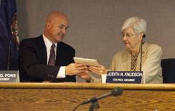 Council member Douglas Pons hands over an iPad to Judith Knudson as they check out the device during a council meeting in Williamsburg, Va.