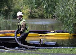 A worker from the Enbridge energy company skims oil from the surface of a Kalamazoo River tributary after a pipeline ruptured in Marshall, Mich., last month.