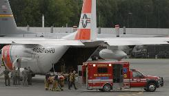 One of the survivors of the plane crash near Dillingham, Alaska, is transferred from a U.S. Coast Guard plane to a waiting Anchorage Fire Department Paramedic rig on Tuesday,