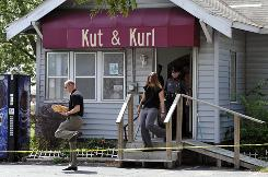 Law enforcement officials leave the Kut & Kurl hair salon in Gentry, Ark., after the business was allegedly robbed by a man and woman early on Wednesday.