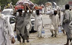 People carry relief supplies through floodwaters in Charsadda in the northwest. The U.N. says 6 million need food.