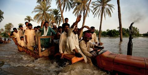 Villagers flee their flooded homes on the back of a truck Wednesday in Muzzaffargarh village in Punjab, Pakistan.