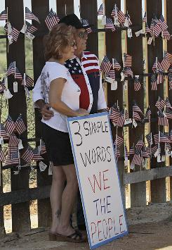 Steve Ellis and Diana Ellis, who were attending the United Border Coalition Tea Party Rally in support of Arizona's immigration law, pose for a picture along the Arizona-Mexico border wall.