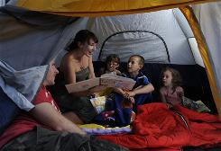 Kevin and Rachel Cashin and their children, Audrey, 6, Aidan, 8, and Abigail, 3, enjoy a bedtime story in the tent in their own backyard.