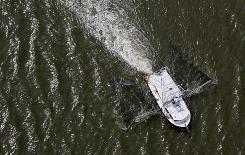 A shrimp boat trolls Louisiana's Barataria Bay on Monday as the fall shrimping season opens.