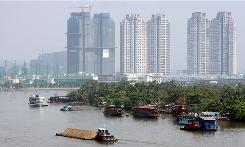 New buildings tower above boats on the Saigon vier in Ho Chi Minh City. The Vietnamese city says its economy grew by 8% last year.