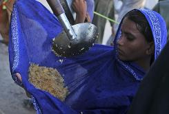 Meals are doled out at a camp in Sukkur, Pakistan. The United Nations says it has received only half of the aid required.