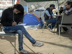Romina Gomez writes a letter to be sent dad Mario Gomez, one of the 33 miners trapped in a gold-and-copper mine near Copiapo, Chile.