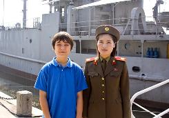 In this photo taken Monday, Jonathan Lee, 13, poses with a North Korean soldier in front of a navy boat during his visit to Pyongyang, North Korea.