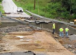 Workers remove debris from a bridge washed out by flooding in the Double Springs community outside Cookeville, Tenn.