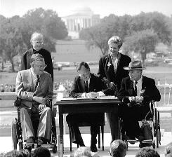 The first President Bush signs the Americans with Disabilities Act during a ceremony on the South Lawn of the White House on July 26, 1990.