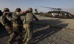 A soldier is helped onto a U.S. Army, 101st Airborne Division, Task Force Destiny medical evacuation helicopter, in Zhari district, Kandahar province, southern Afghanistan, Friday.