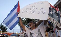 "Cuban exile Oscar Gala shouts anti-Castro slogans as he protests in Miami, July 30. The sign in Spanish on the left reads ""The Art Of Killing Prisoners"", and on the right, ""Orlando Zapata Tamayo Murdered For Claiming Human Rights""."
