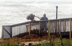 Sergio Alvarez cleans a boardwalk in South Padre Island, Texas, after remnants of the season's first hurricane, Alex, passed through in late June