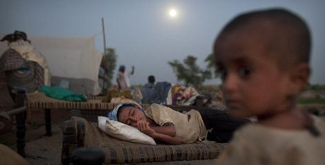 A Pakistani girl forced to flee flooding from her village sleeps on a bed on the roadside at a makeshift camp the city of Shadad Kot, in Sindh province, southern Pakistan, Monday, Aug. 23.
